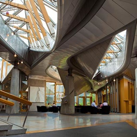Image of the garden lobby inside Scottish Parliament. There are stairs to the left of the image and seats in the distance